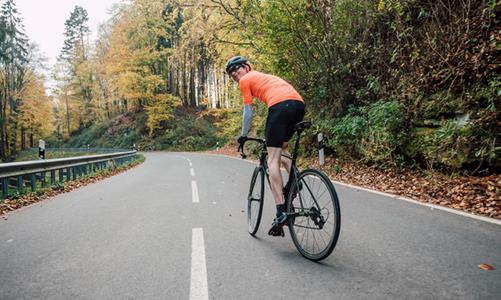 山道を自転車で登る男性