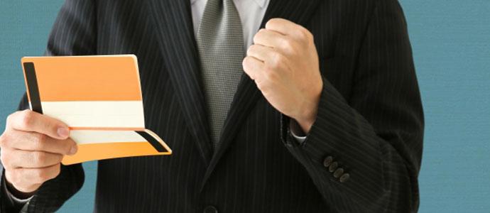 競輪で儲けた通帳を見てガッツポーズする男性